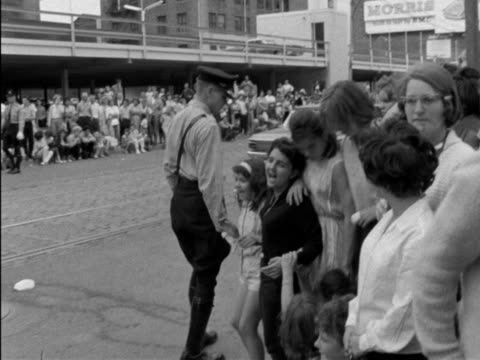 beatlemania - shots of beatles fans waiting for their idols / shot of sign reading st. james cathedral, to teenagers sitting on curb holding signs /... - attività equestre ricreativa video stock e b–roll