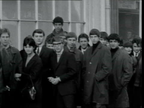 beatles fans queue for beatles-type boots; england: london: great queen st: anello & david: ext long queue of teenagers outside shop: pan along... - the beatles stock videos & royalty-free footage