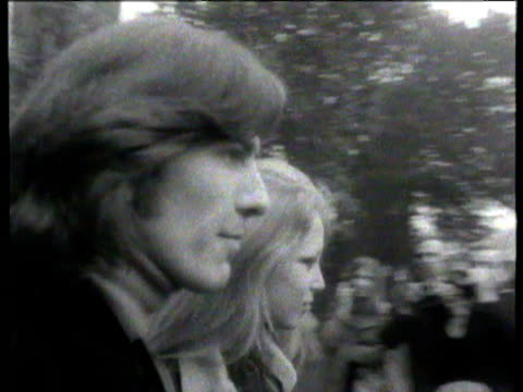 beatles member george harrison with wife pattie boyd leaving court after answering drug charges / pair surrounded by press as they leave court and... - the beatles stock videos & royalty-free footage