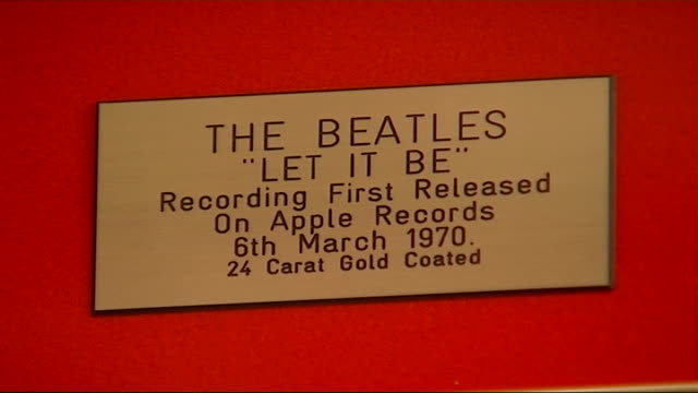 London INT Special collectable gold and silver vinyl Beatles records displayed in record shop / Closeup plaque on Beatles 'Let It Be' record / Framed...
