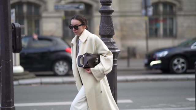 stockvideo's en b-roll-footage met beatrice gutu wears sunglasses, a white long coat, a brown jacket, white shoes, a bag, cuffed pants, outside paul smith, during paris fashion week -... - manchet mouw