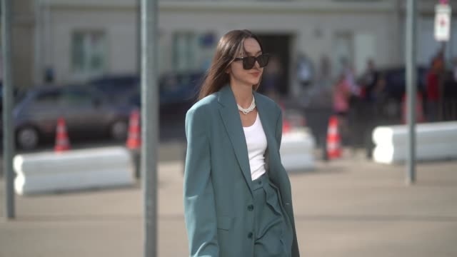 beatrice gutu wears sunglasses, an oversized blazer jacket, a white t-shirt, flare pants, a necklace, outside acne, during paris fashion week - haute... - maglietta video stock e b–roll