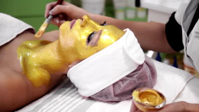 vídeos de stock e filmes b-roll de terapeuta de beleza aplica cosmetology mudpack no cliente's neck - máscara facial