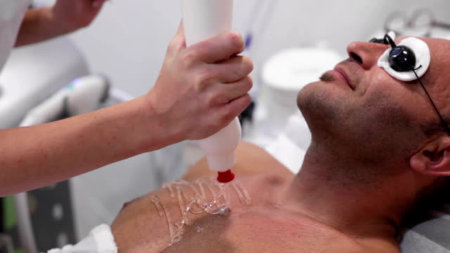stockvideo's en b-roll-footage met beautician applies gel  on patient's chest for laser hair removal - borstkas