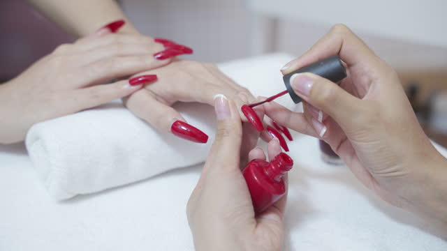 beautician applies red nail polish to a young womans nails. - fingernail stock videos & royalty-free footage