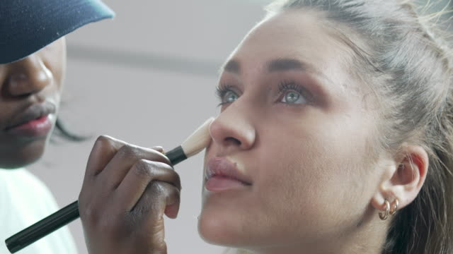 a beautician applying blusher to a models face - beauty stock videos & royalty-free footage
