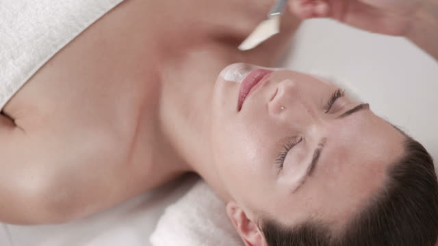 stockvideo's en b-roll-footage met hd: beautician applying facial mask to woman's face - spa treatment