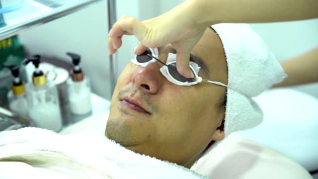 vídeos de stock e filmes b-roll de 4k beautician doctor wearing light protective eyepatch safety glasses goggles ipl to handsome man patient eye at beauty salon - depilação