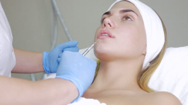 beautician makes the procedure against wrinkles beautiful young woman. - viziarsi video stock e b–roll
