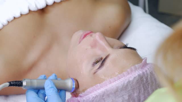 kosmetikerin macht das verfahren gegen falten schöne junge frau. - schönheitssalon stock-videos und b-roll-filmmaterial