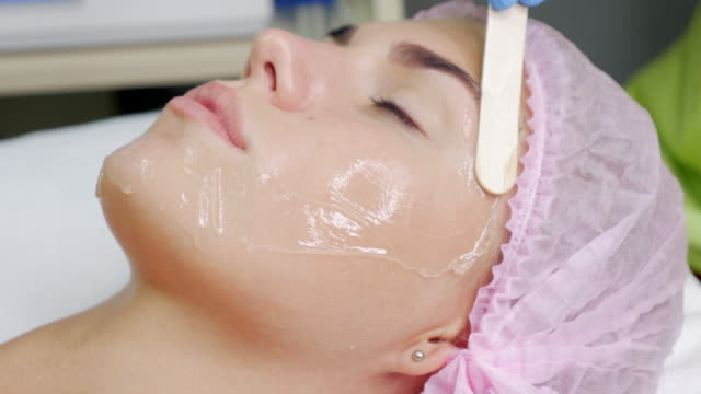 beautician makes the procedure against wrinkles beautiful young woman. - beautician stock videos and b-roll footage