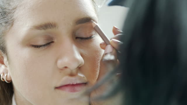 a beautician using an eybrow pencil to colour in a models eyebrows - eyebrow stock videos & royalty-free footage
