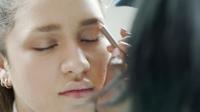 vídeos de stock, filmes e b-roll de uma esteticista usando um lápis de eybrow para colorir em sobrancelhas modelos - sobrancelha