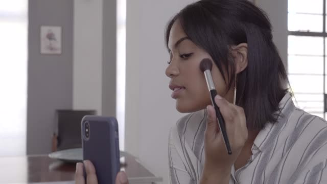 beautician using blush while recording video on phone - tutorial stock videos and b-roll footage
