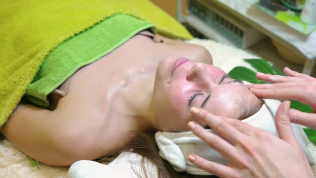 beautician using face cream to gently massage the face after a facial treatment - facial massage stock videos and b-roll footage