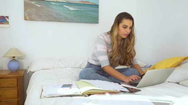 A beautifu girl studying in a bright bedroom with notes and laptop