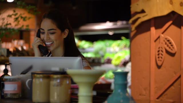 彼女はそれをシステムに追加しながら予約する顧客から電話を受けるレストランの美しい管理者 - 応答する点の映像素材/bロール
