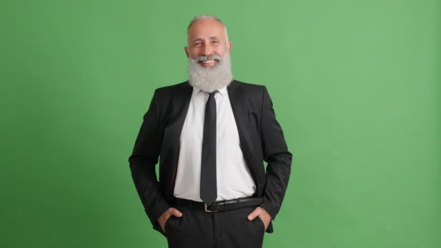 Beautiful adult businessman looking at the camera and smiling on a green background