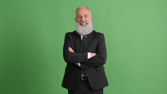 vídeos de stock, filmes e b-roll de lindo empresário adulto olhando para a câmera e sorrindo sobre um fundo verde - 50 59 years