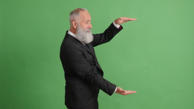 beautiful adult businessman shows copy space and crosses his hands on a green background - big hair stock videos & royalty-free footage