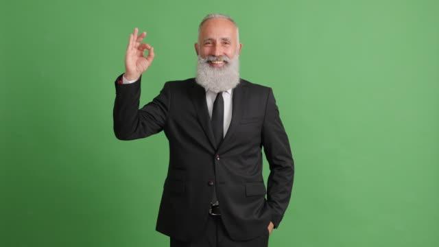 vídeos de stock, filmes e b-roll de lindo adulto empresário mostra okey sobre um fundo verde - 50 59 years