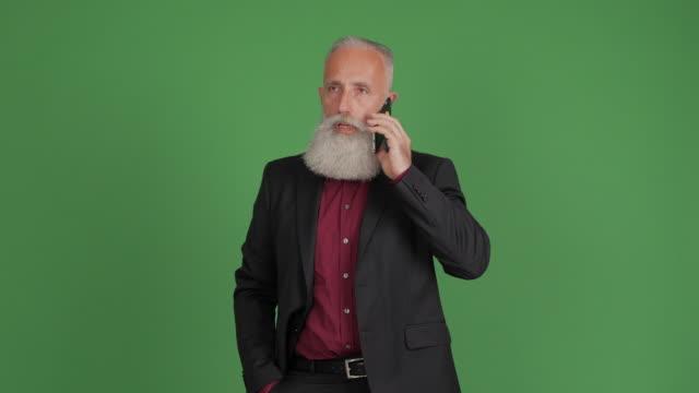 vackra vuxen affärsman talar på din smartphone på en grön bakgrund - 50 59 years bildbanksvideor och videomaterial från bakom kulisserna
