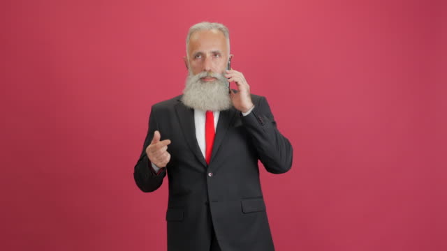 beautiful adult businessman speaks on the smartphone on a red background - 50 59 years video stock e b–roll
