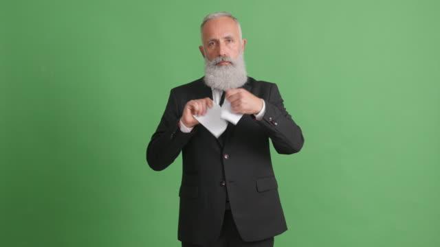 schöne erwachsene geschäftsmann reißt ein blatt papier auf einem grünen bildschirm - 50 59 years stock-videos und b-roll-filmmaterial