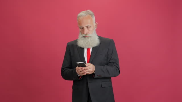 beautiful adult businessman uses a smartphone for message on a red background - 50 59 years video stock e b–roll