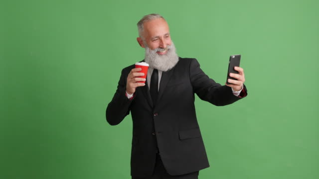 Beautiful adult businessman uses a smartphone for selfie on a green background