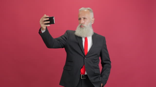 beautiful adult businessman uses a smartphone for selfie on a red background - 50 59 years video stock e b–roll