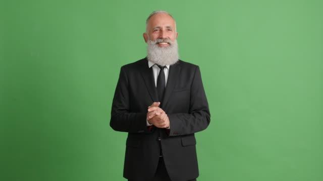 vídeos de stock, filmes e b-roll de lindo adulto empresário com um sorriso parece em torno de si um fundo verde - 50 59 years