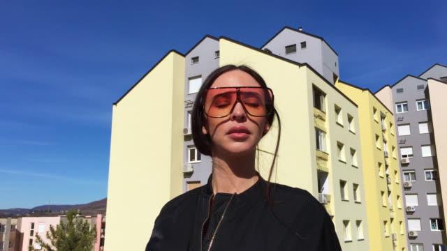 schöne erwachsenenfrau mit sonnenbrille im freien mit wolkenkratzern im hintergrund - sonnenbrille stock-videos und b-roll-filmmaterial