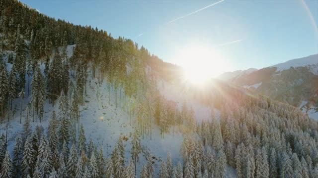 schöne luftaufnahmen drohne schuss über die kalten landschaften der schweiz, enthüllt die sonne flares in den schnee berggipfel begrenzt - wintersport stock-videos und b-roll-filmmaterial