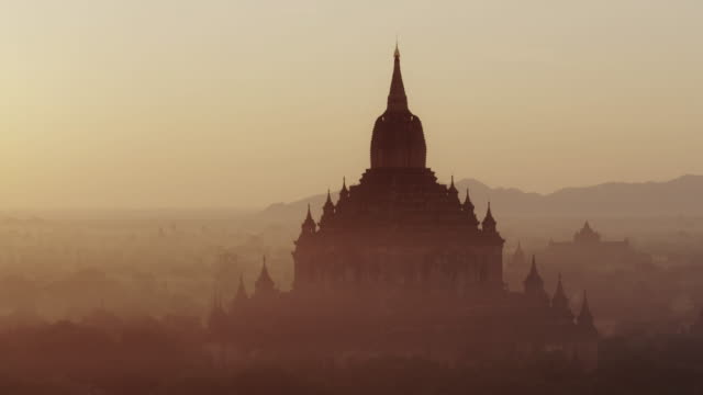 beautiful aerial move on large ancient temple at sunrise in myanmar - myanmar stock videos & royalty-free footage