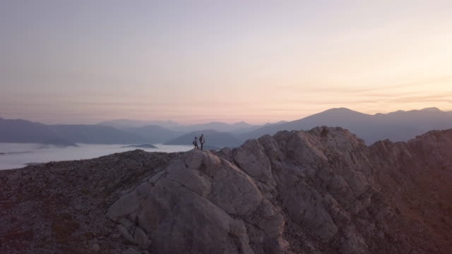 beautiful aerial view during sunrise of a couple on the top of a mountain - ganz oben stock-videos und b-roll-filmmaterial