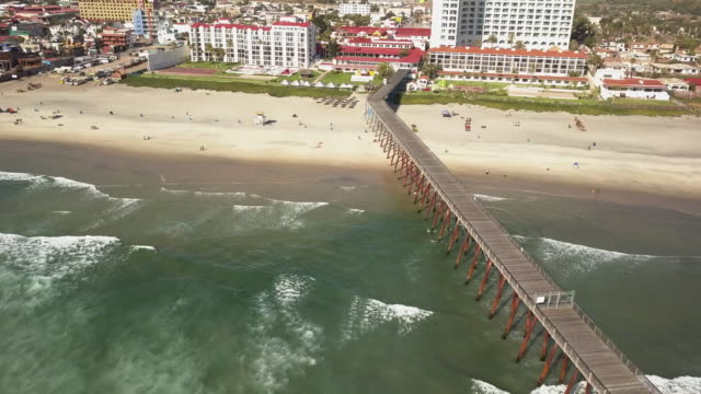 a beautiful aerial view of the pier on rosarito beach in the baja peninsula - baja california norte stock videos & royalty-free footage