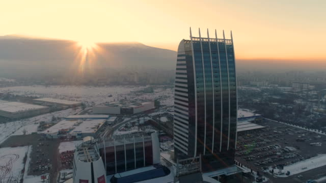 beautiful aerial view of the setting sun behind a mountain near financial district in sofia - bulgaria video stock e b–roll