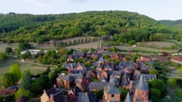 Beautiful aerial view over the village of Collonges-La-Rouge in France. The village is in the middle of a forest and green fields.