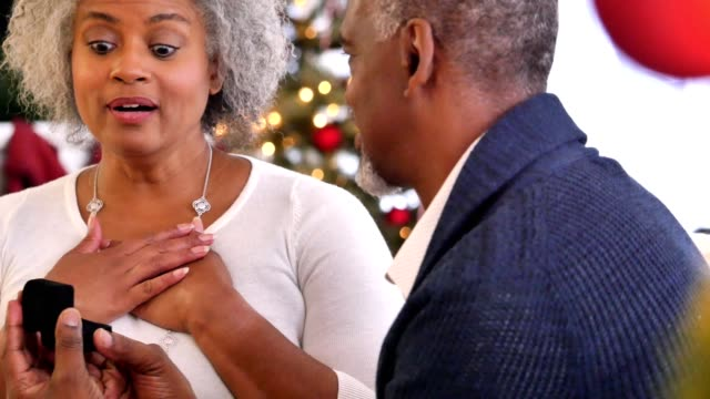 Beautiful African American senior woman receives jewelry gift from husband