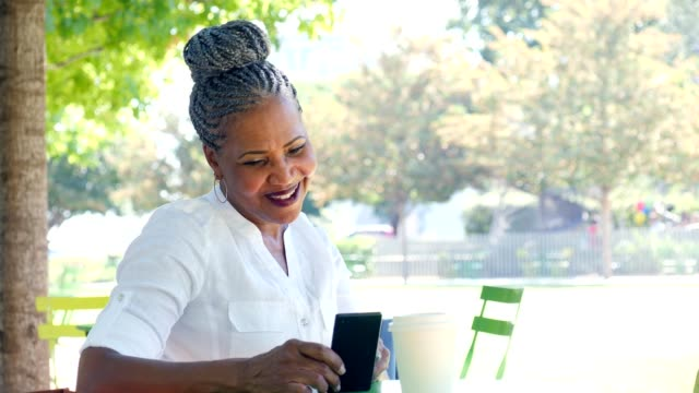 beautiful african american senior woman uses smartphone while sitting outdoors - one senior woman only stock videos & royalty-free footage