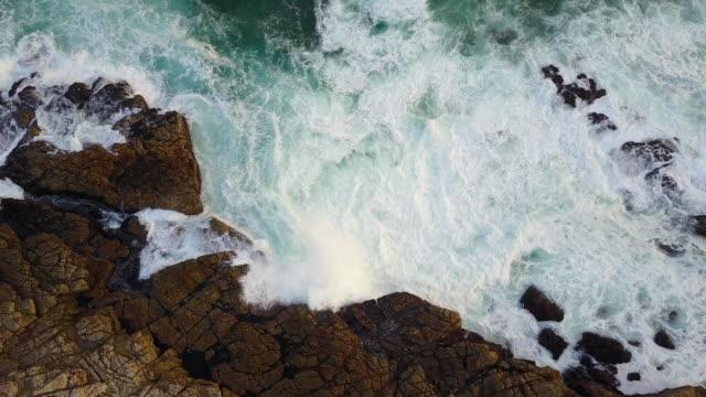 vídeos y material grabado en eventos de stock de costa africana hermosa con olas rompiendo contra las rocas - mirar hacia abajo