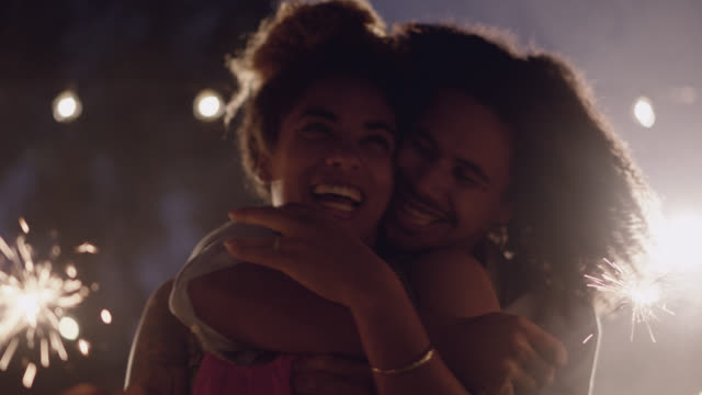 vídeos de stock e filmes b-roll de slo mo. beautiful african-american couple holding sparklers dance, hug and kiss - namorado