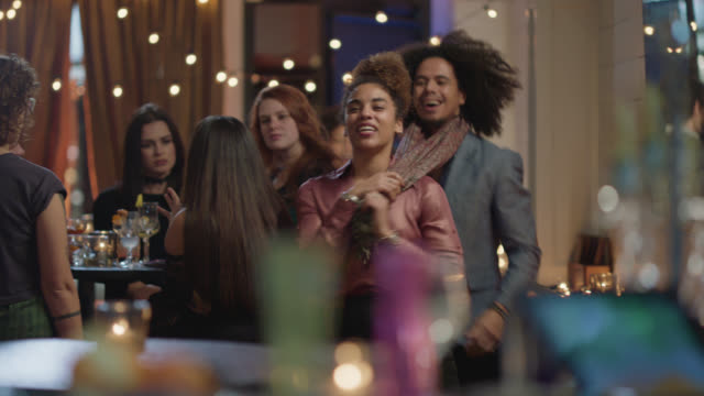 vídeos y material grabado en eventos de stock de a beautiful african-american woman playfully leads her friends into a bar and waves to the bartender - 30 34 años