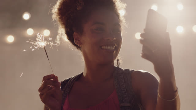 slo mo. beautiful african-american woman takes a selfie holding a sparkler - only mid adult women stock videos & royalty-free footage