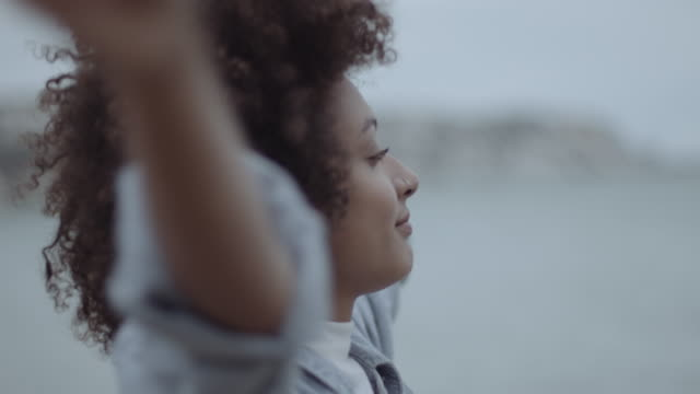 beautiful afro black woman on the beach near sea contemplating serene at autumn with hands in air - mixed race person stock videos & royalty-free footage
