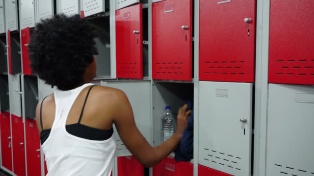 beautiful afro woman putting away her stuff in the locker room at the gym - black stock videos & royalty-free footage