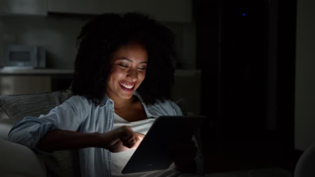vídeos de stock, filmes e b-roll de linda mulher afro jovem em casa relaxando no sofá à noite navegando em suas redes sociais rindo e sorrindo - jornal