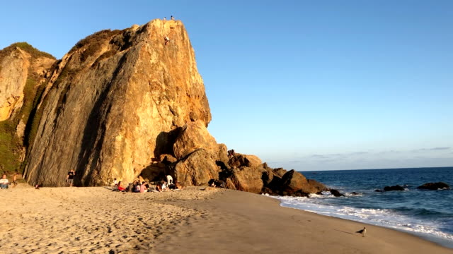 beautiful afternoon at zuma beach in malibu with climbers enjoying the rock wall. - malibu stock videos & royalty-free footage