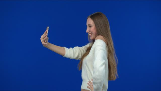 セーターで美しく、幸せな女の子は、スマートフォンで自分撮りを取って笑顔を楽しんでいます。 - 絵画モデル点の映像素材/bロール